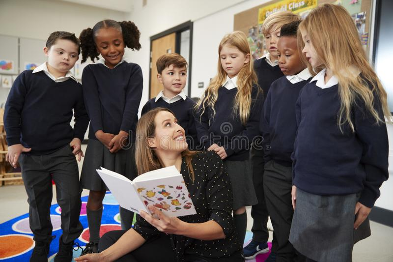 Primary school teacher reading a book in class turning around to look at the kids. Standing behind her, front view stock image