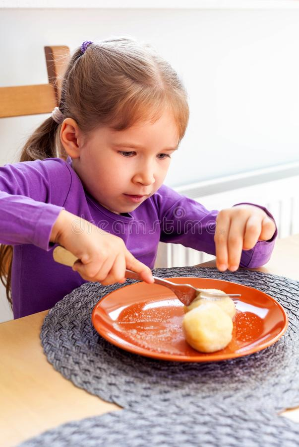 Primary school young girl sitting on a chair near a table, eating potato dumplings all by herself, holding a fork in her hands. Cutting the food. Child using royalty free stock image