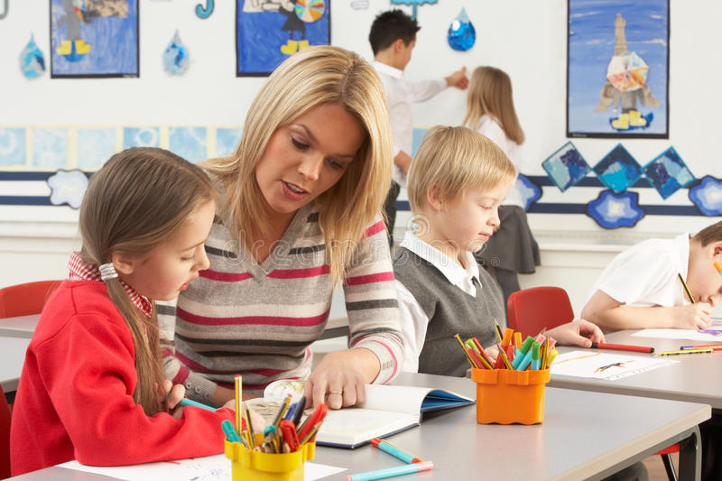 Primary Schoolchildren And Teacher Having A Lesson stock photography