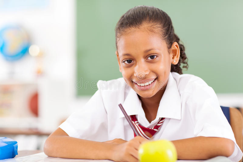Primary student. Young female primary student sitting in classroom royalty free stock photos
