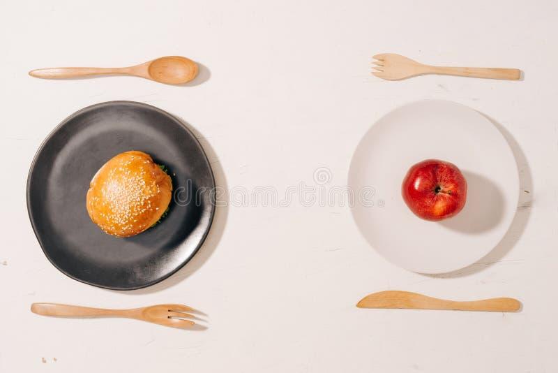 Primat dilemma mellan sund bra ny frukt och grönsaker eller rik snabbmat för kolesterol royaltyfri fotografi