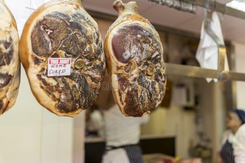 Primat och högvärdigt hem- kurerat griskött fogar ihop att hänga i slaktare arkivfoton