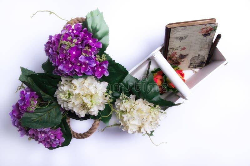 Primavera benvenuta - mazzo di fiori, di canestro di legno bianco e di taccuino immagini stock libere da diritti