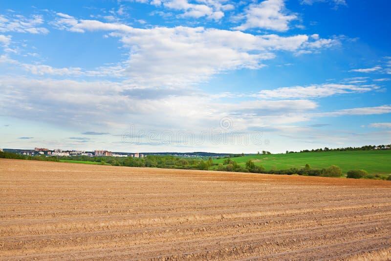 Primavera di paesaggio con il campo ed il cielo blu arati immagini stock