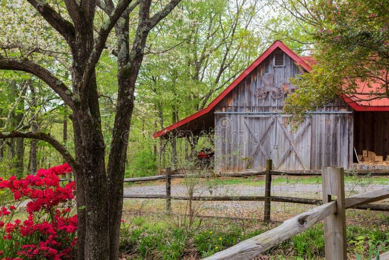 Primavera en el país con un granero rojo-cubierto y los árboles imágenes de archivo libres de regalías