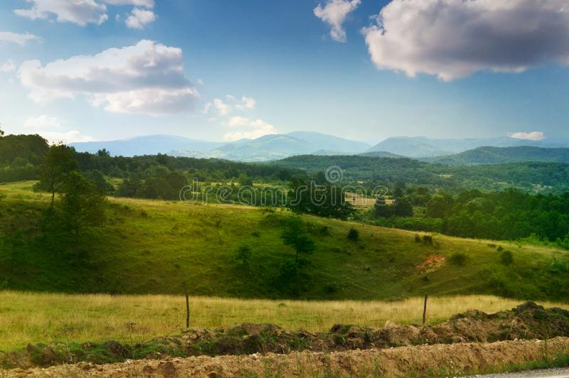 Primavera, Rolling Hills y molino de viento de Toscana en paisaje rural de la puesta del sol fotografía de archivo