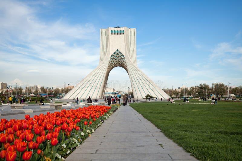 Primavera a Teheran con i tulipani rossi davanti al monumento di Azadi immagini stock libere da diritti