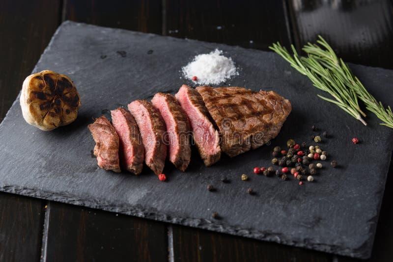 sliced prime ribeye steak on black stone plate medium degree of