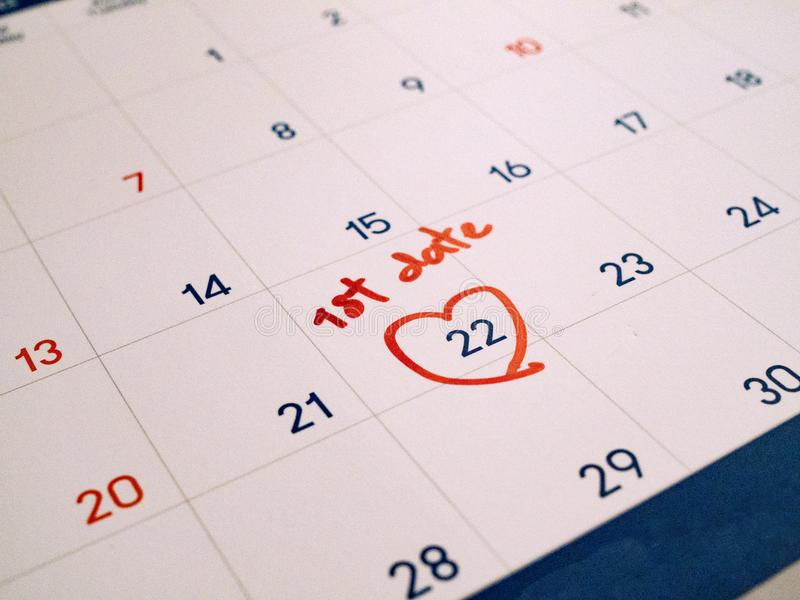 Primeira data do vermelho marcada na data-alvo branca da agenda do calendário para o romance e datar imagens de stock