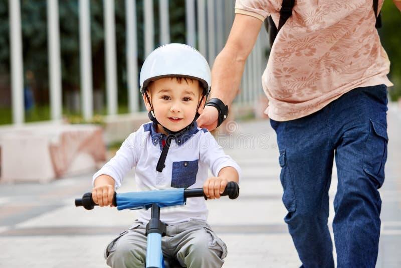 Primeira equitação da bicicleta das lições O pai ensina seu filho montar uma bicicleta imagens de stock royalty free