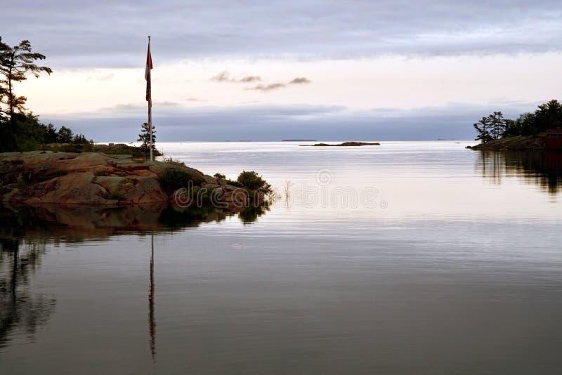 A primeira luz revela o mastro de bandeira na entrada ao canal de Killarney, Killarney, Ontário fotos de stock royalty free