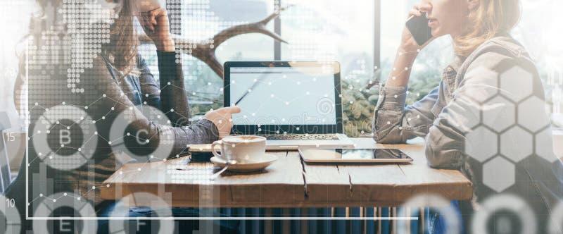 A primeira menina que mostra o lápis no tela de computador, outro está falando no telefone celular imagem de stock royalty free