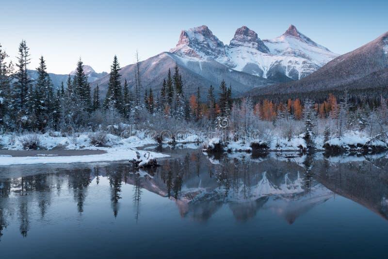 Primeira neve Quase perfeita reflexo dos picos das três irmãs no rio Bow Canmore em Banff National Park Canadá foto de stock royalty free