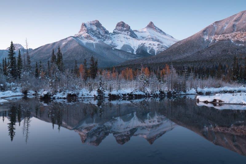 Primeira neve Quase perfeita reflexo dos picos das três irmãs no rio Bow Canmore em Banff National Park Canadá fotografia de stock royalty free