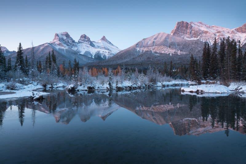 Primeira neve Quase perfeita reflexo dos picos das três irmãs no rio Bow Canmore em Banff National Park Canadá imagem de stock royalty free