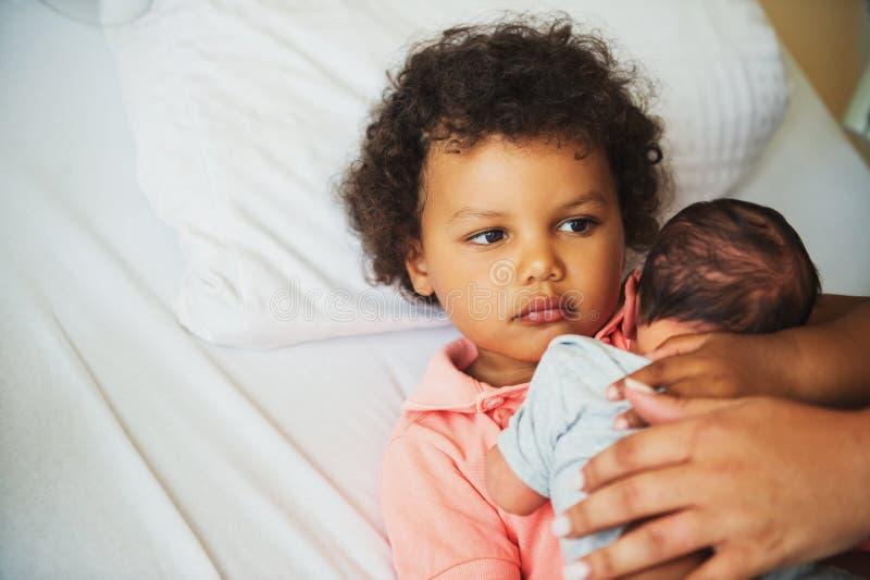 Primeira reunião do menino africano adorável da criança e de seu irmão recém-nascido imagens de stock