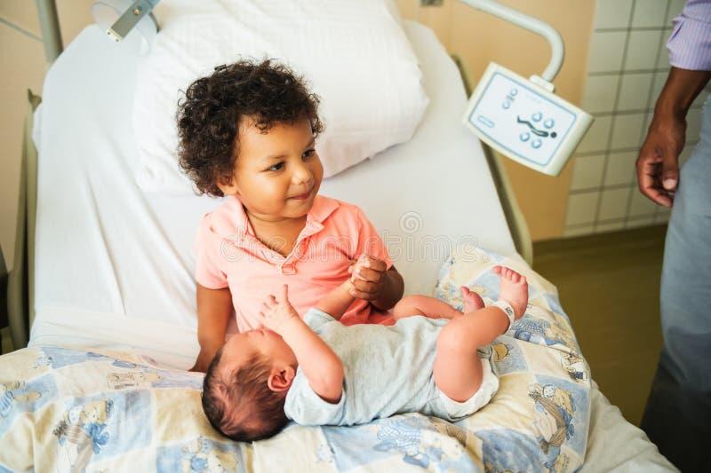 Primeira reunião do menino africano adorável da criança e de seu irmão recém-nascido imagem de stock royalty free