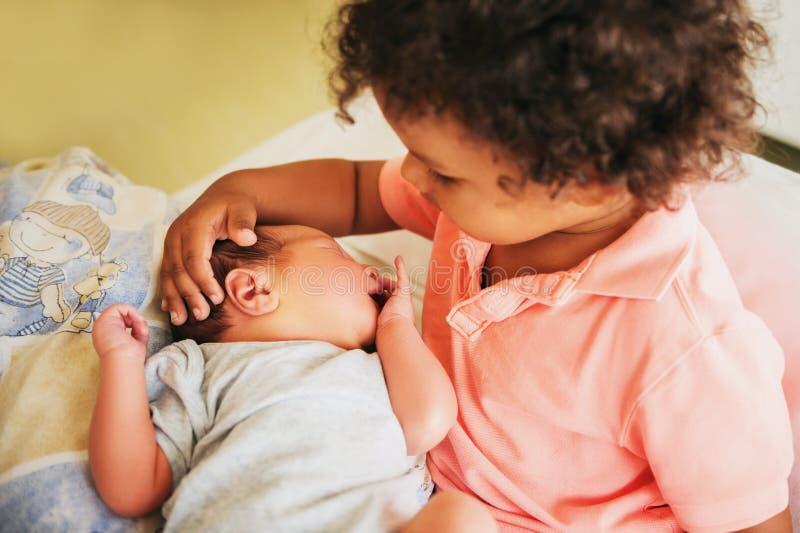 Primeira reunião do menino africano adorável da criança e de seu irmão recém-nascido fotografia de stock royalty free