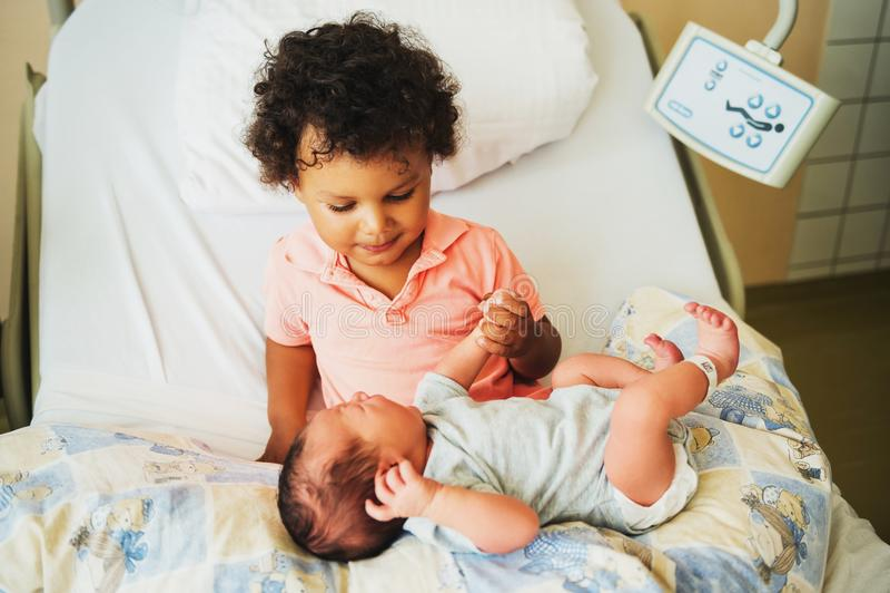 Primeira reunião do menino africano adorável da criança e de seu irmão recém-nascido fotos de stock royalty free