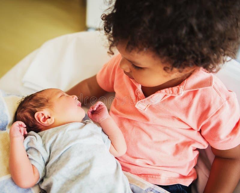 Primeira reunião do menino africano adorável da criança e de seu irmão recém-nascido foto de stock royalty free