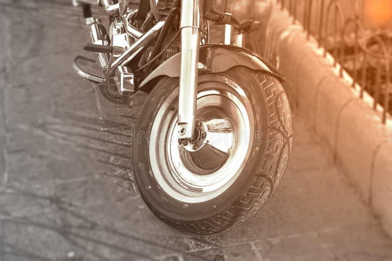 A primeira roda da bicicleta preto e branco do motor estacionou na rua da cidade foto de stock royalty free