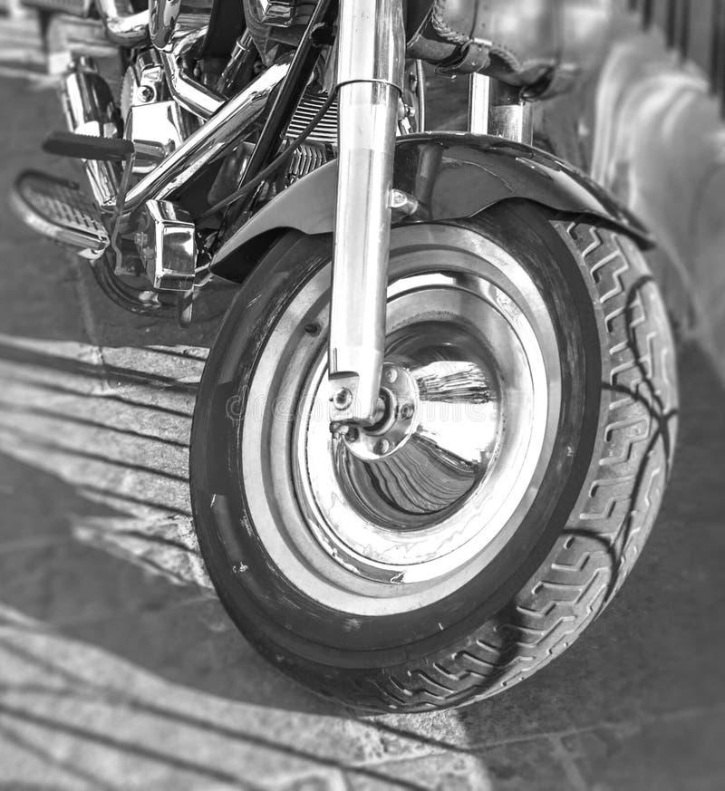 A primeira roda da bicicleta preto e branco do motor estacionou na rua da cidade fotos de stock royalty free