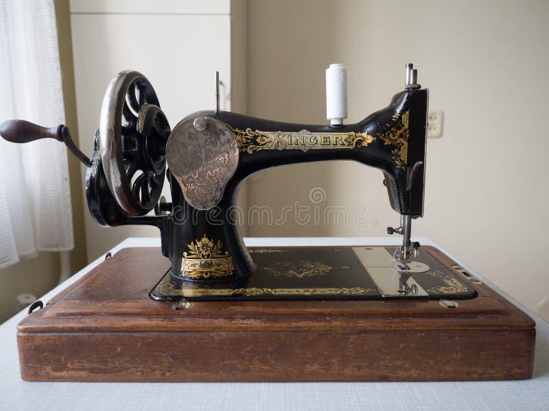 Primeiramente - máquina de costura do CANTOR da mão, foco seletivo foto de stock