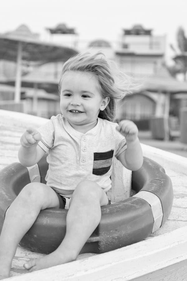 Primeiras férias com pontas e conselho da criança A criança do menino senta-se no boia salva-vidas A criança aprecia férias na pr fotografia de stock royalty free