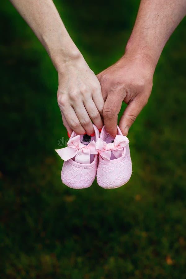 Primeiras sapatas do bebê nas mãos de um pai fotografia de stock royalty free