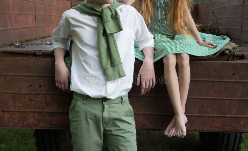Primeiro amor não recompensado uma menina descalça em um vestido verde senta-se na parte de trás de um carro e abraça-se a com os fotos de stock royalty free
