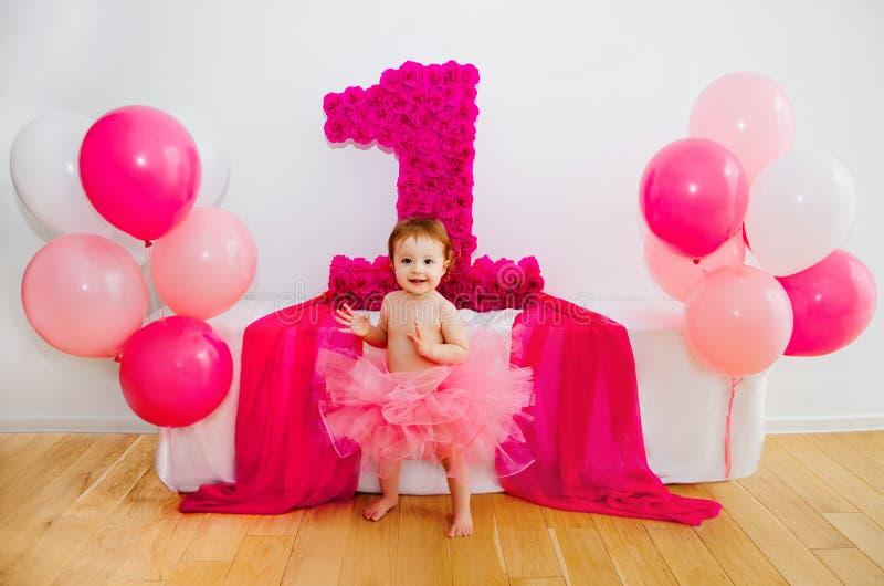 Primeiro aniversário Bebê na saia cor-de-rosa macia, com balões e um bi fotografia de stock