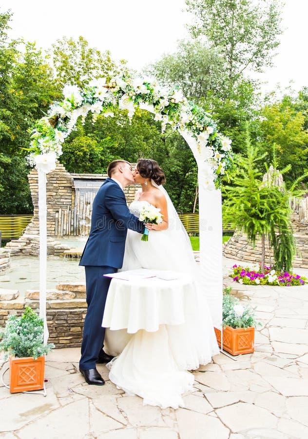 Primeiro beijo recentemente do casal sob o arco do casamento fotografia de stock royalty free