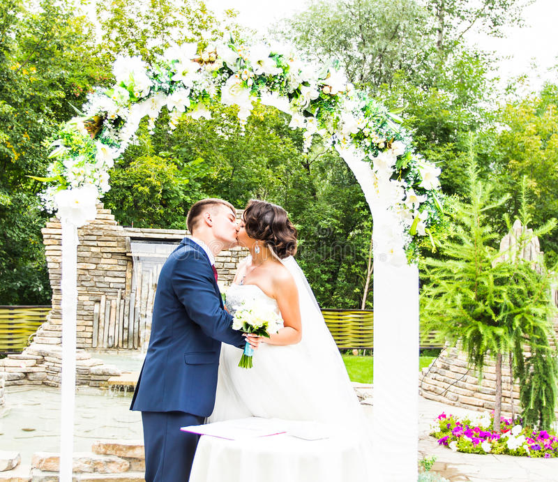 Primeiro beijo recentemente do casal sob o arco do casamento fotos de stock royalty free