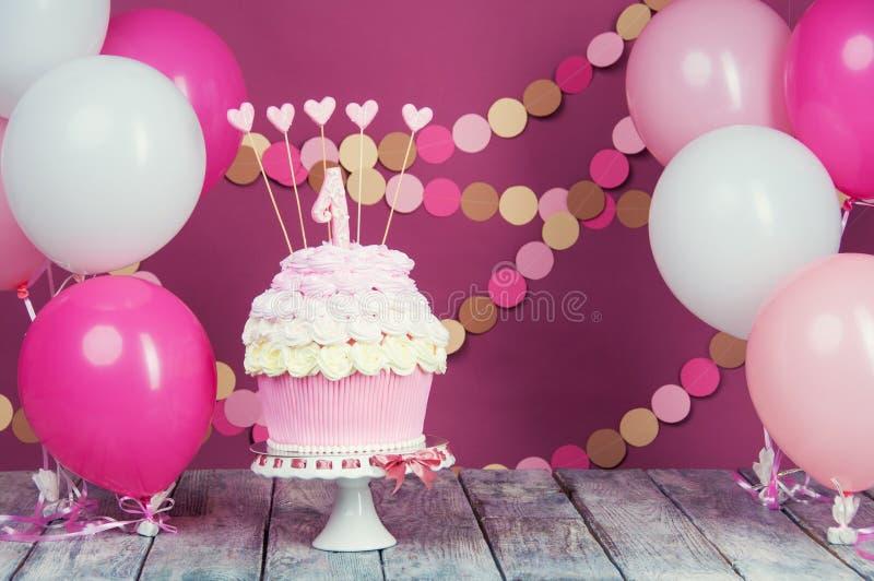 Primeiro bolo de aniversário com uma unidade em um fundo cor-de-rosa com bolas e a festão de papel imagens de stock