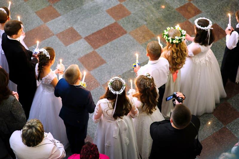 Primeiro comunhão santamente na igreja, muitas crianças imagens de stock