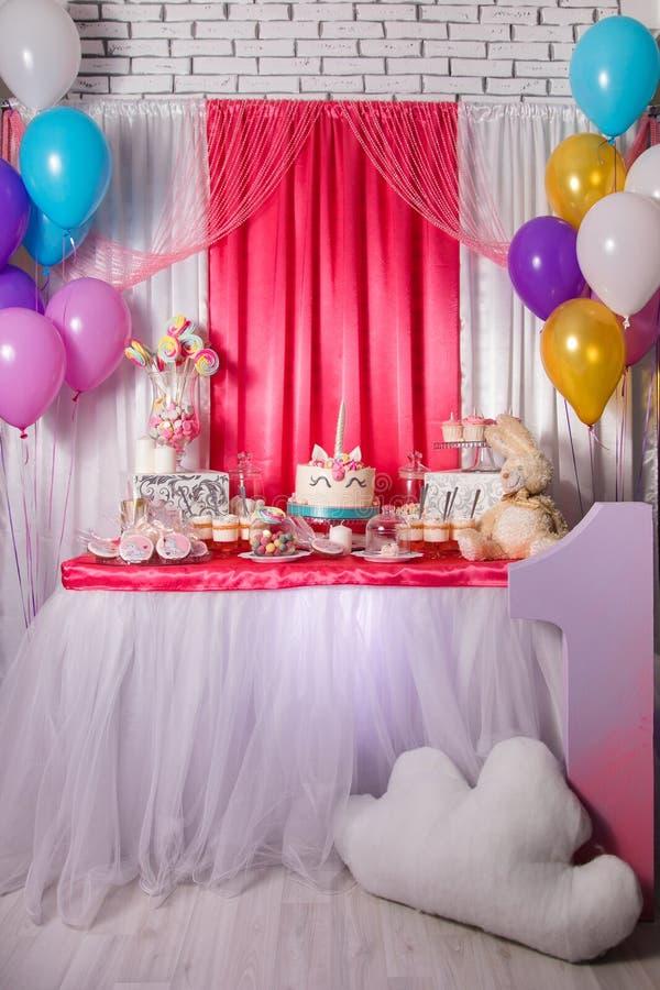 Primeiro conceito da festa de anos do bebê Barra de chocolate com os bolos do unicórnio e artigos doces da decoração em cores cor imagens de stock
