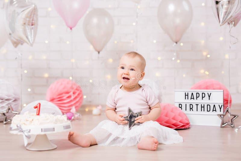 Primeiro conceito do aniversário - menina de sonho engraçada e bolo de aniversário despedaçado com luzes, estrelas e balões fotografia de stock royalty free
