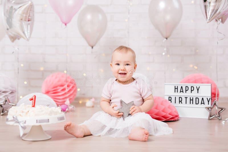 Primeiro conceito do aniversário - menina suja engraçada e bolo de aniversário despedaçado com luzes e balões imagem de stock