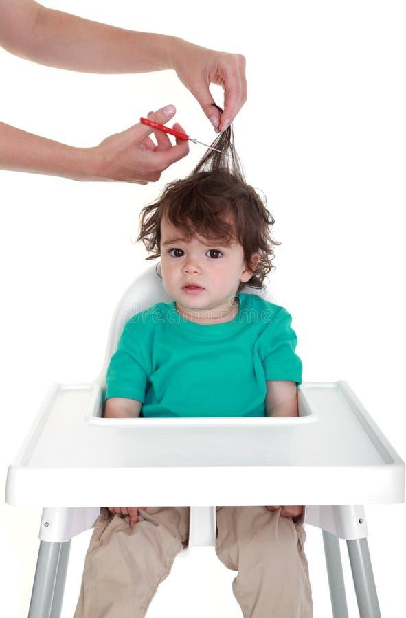 Primeiro corte de cabelo do bebê imagem de stock