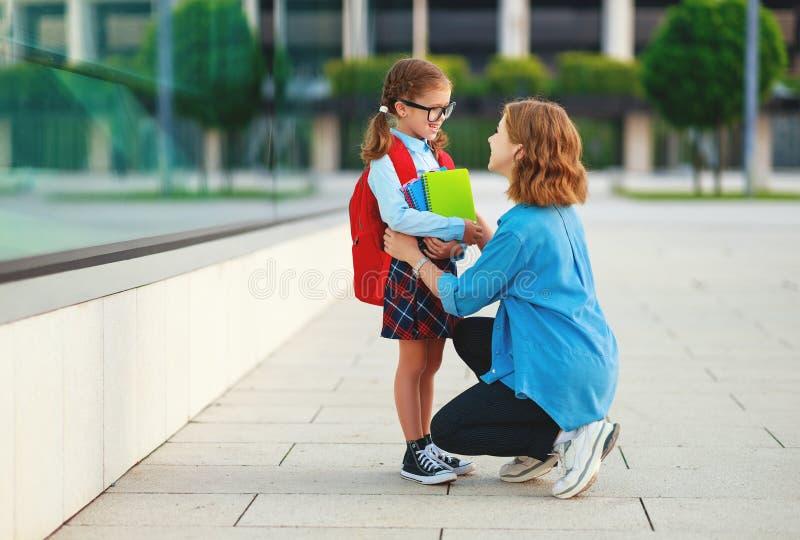 Primeiro dia na escola a mãe conduz a menina da escola da criança pequena em de primeiro grau fotos de stock royalty free