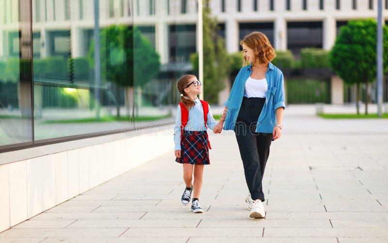 Primeiro dia na escola a mãe conduz a menina da escola da criança pequena em de primeiro grau fotos de stock