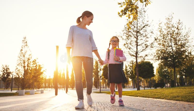 Primeiro dia na escola a mãe conduz a menina da escola da criança pequena em f fotos de stock