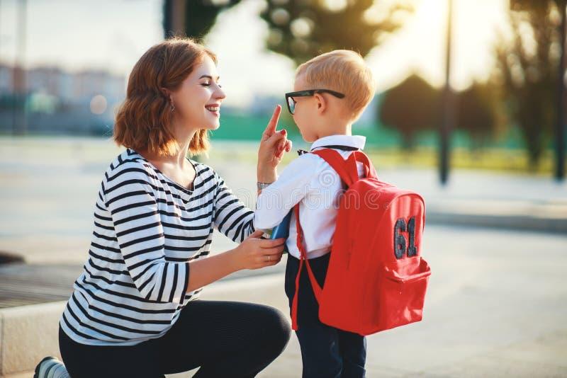 Primeiro dia na escola a mãe conduz o menino de escola da criança pequena em de primeiro grau fotografia de stock