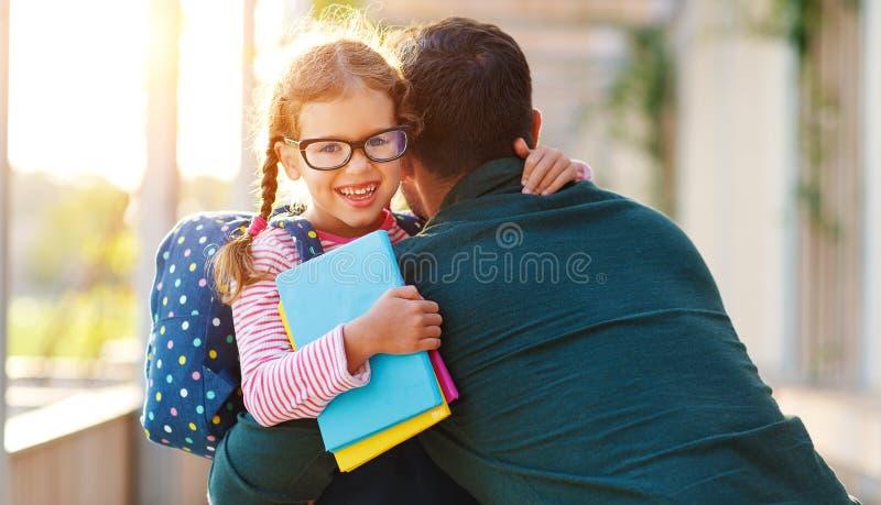Primeiro dia na escola o pai conduz a menina da escola da criança pequena em de primeiro grau imagens de stock