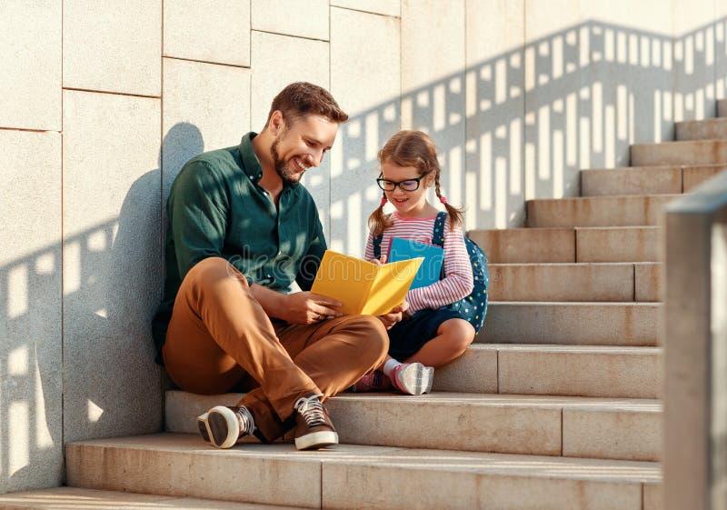 Primeiro dia na escola o pai conduz a menina da escola da criança pequena em de primeiro grau imagem de stock royalty free