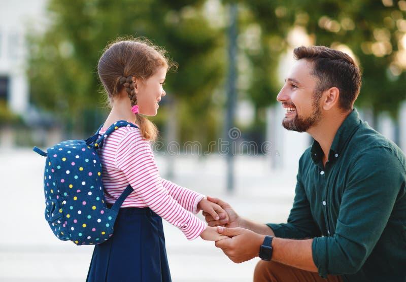 Primeiro dia na escola o pai conduz a menina da escola da criança pequena em de primeiro grau imagens de stock royalty free
