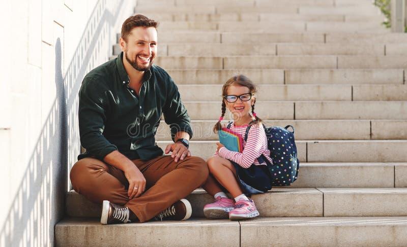 Primeiro dia na escola o pai conduz a menina da escola da criança pequena em de primeiro grau foto de stock royalty free