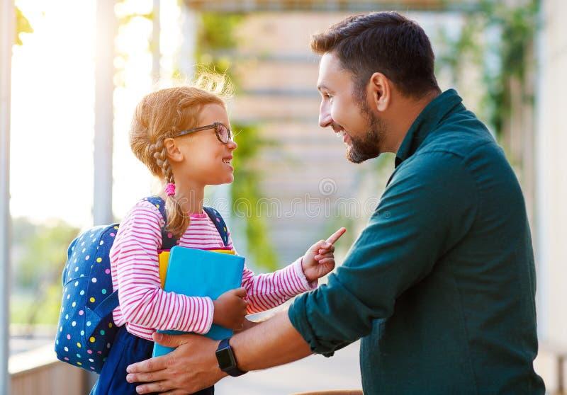 Primeiro dia na escola o pai conduz a menina da escola da criança pequena em de primeiro grau imagem de stock