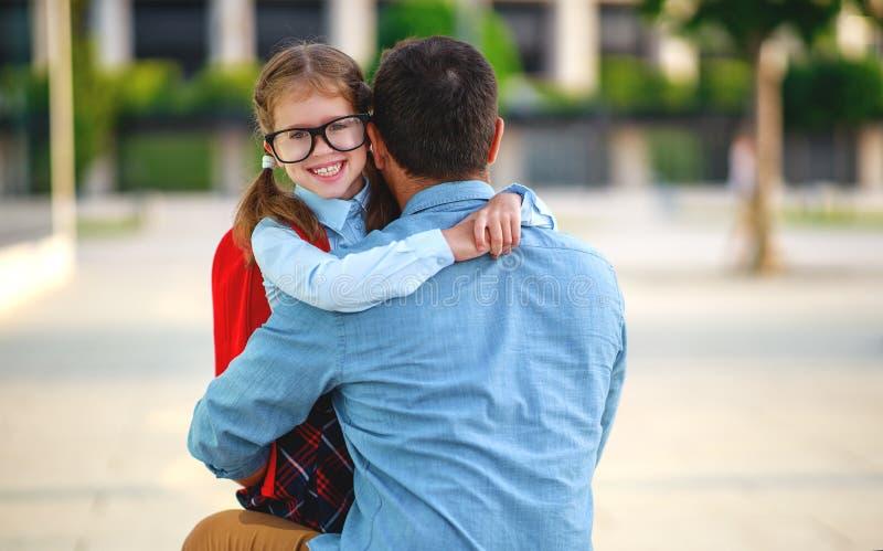 Primeiro dia na escola o pai conduz a menina da escola da criança pequena em de primeiro grau foto de stock