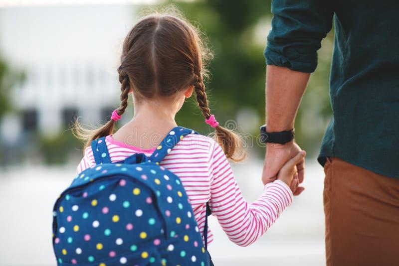 Primeiro dia na escola o pai conduz a menina da escola da criança pequena em f fotos de stock royalty free